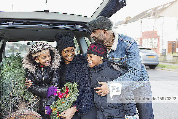 Glückliche Familie mit Weihnachtsbaum im Auto