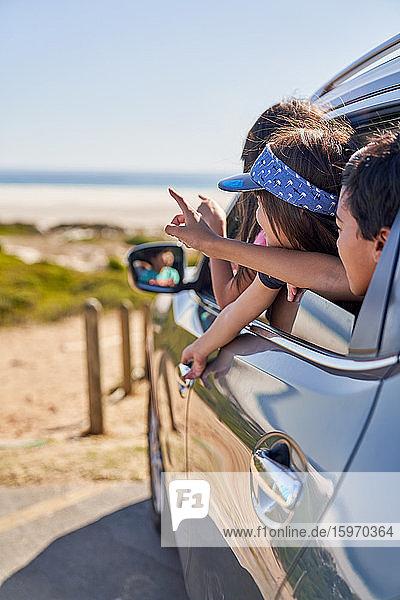 Glückliche Kinder  die sich am Strand aus dem Autofenster lehnen
