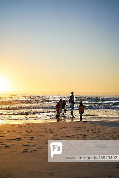 Familie watet bei Sonnenuntergang am Strand in der Brandung