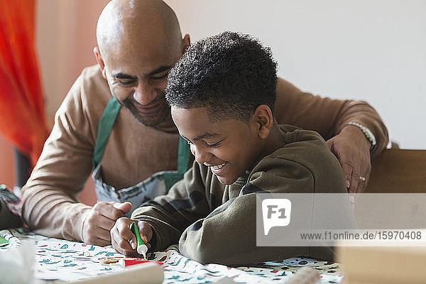 Glückliche Vater und Sohn schmücken Weihnachtsplätzchen