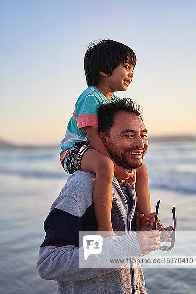 Glücklicher Vater trägt seinen Sohn auf den Schultern am Strand des Ozeans