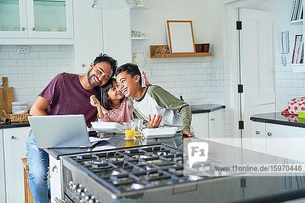 Verspielter Vater und Kinder essen und Laptop in der Küche benutzen