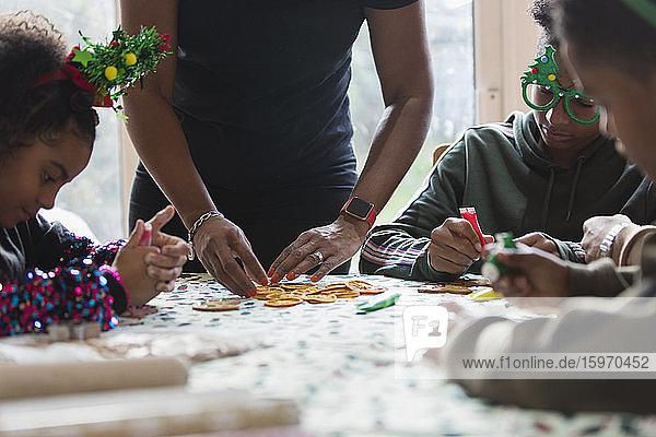 Familie schmückt Weihnachtsplätzchen bei Tisch