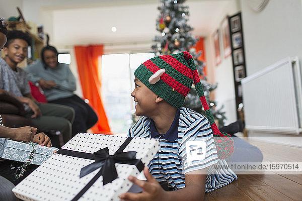 Aufgeregter Junge öffnet Weihnachtsgeschenk auf Wohnzimmerboden