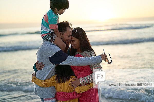 Glückliche  liebevolle Familie umarmt sich bei Sonnenuntergang am Meeresstrand