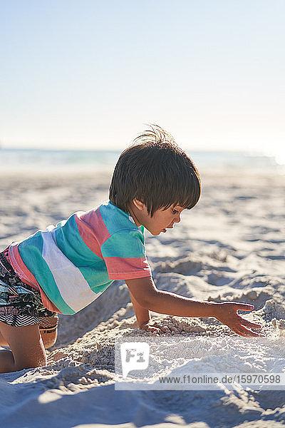 Junge spielt im Sand am sonnigen Sommerstrand
