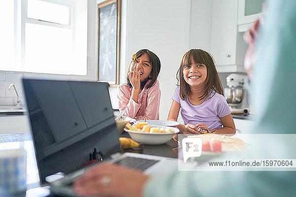 Glückliche Schwestern frühstücken in der Küche  während die Mutter am Laptop arbeitet