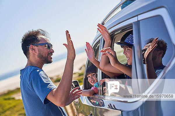 Vater mit fünf Kindern im Auto am sonnigen Strand