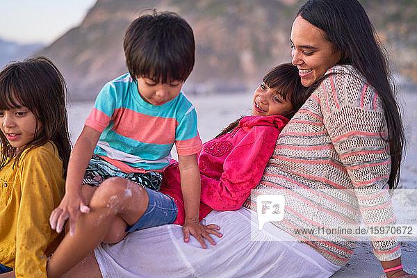 Glückliche Mutter und Kinder entspannen am Strand