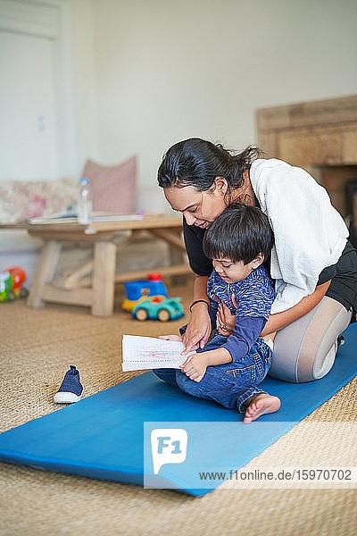 Sohn zeigt Mutter beim Zeichnen auf Yogamatte