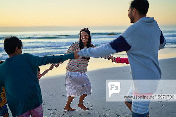 Glückliche Familie hält am Strand im Kreis Händchen
