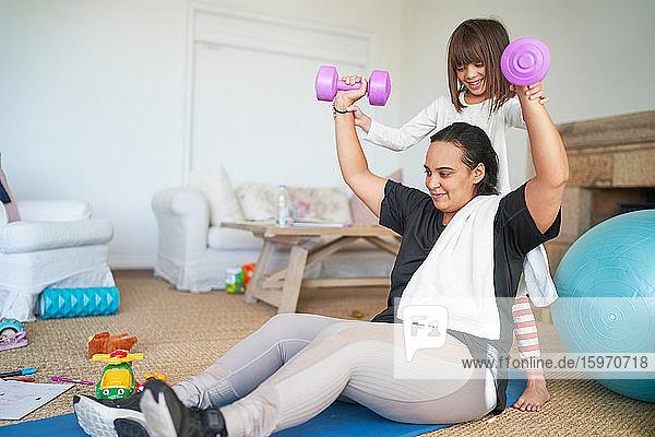 Tochter hilft Mutter beim Training mit Hanteln im Wohnzimmer