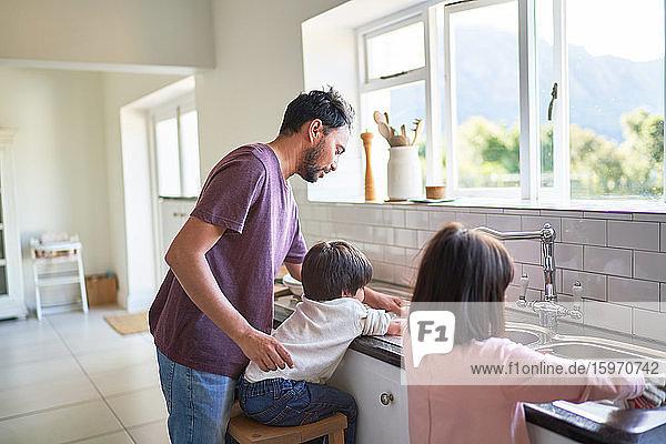 Vater und Kinder beim Abwasch an der Küchenspüle