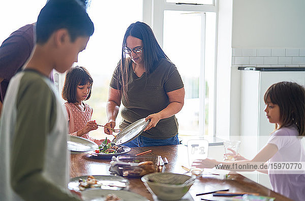 Familie räumt Essen und Geschirr vom Mittagstisch