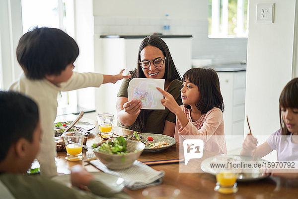 Mutter und Kinder beim Mittagessen am Esstisch