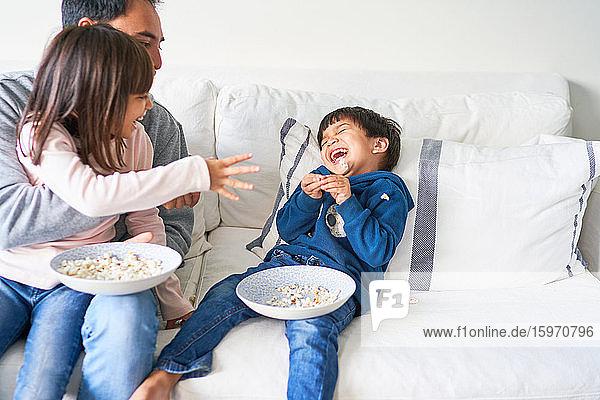Verspielte Familie mit Popcorn auf dem Wohnzimmersofa