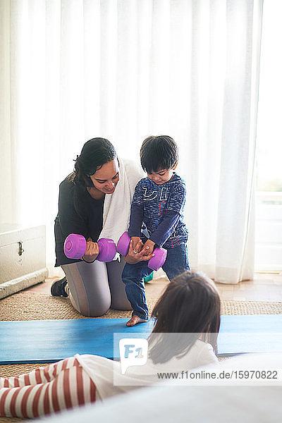Mutter und Kinder üben mit Hanteln im Wohnzimmer