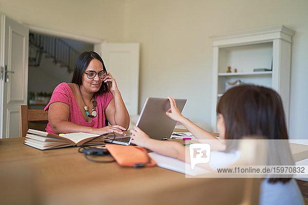 Tochter lenkt Mutter bei der Arbeit am Laptop im Esszimmer ab