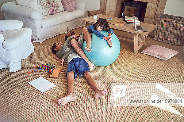 Spielerischer Vater und Kinder mit Fitnessball auf dem Wohnzimmerboden