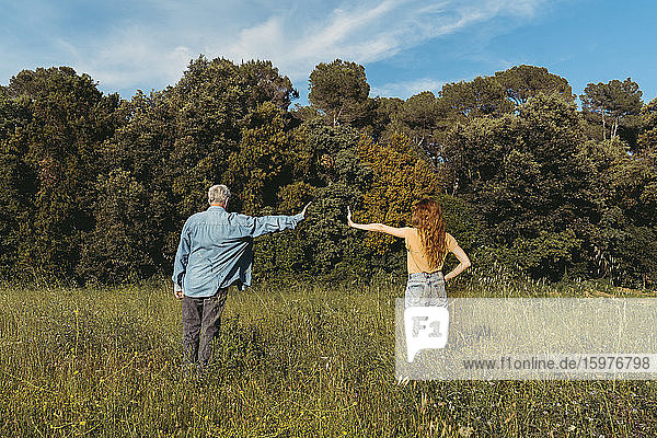 Rear view of woman and senior man with masks standing on meadow  safety distance