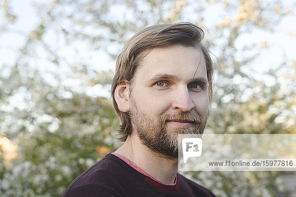 Close-up portrait of confident bearded man at back yard