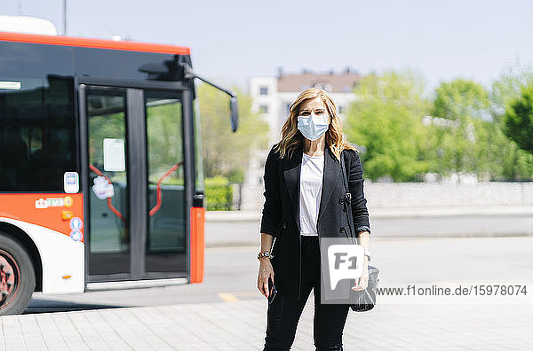 Portrait of mature woman wearing protective mask waiting at bus stop  Spain
