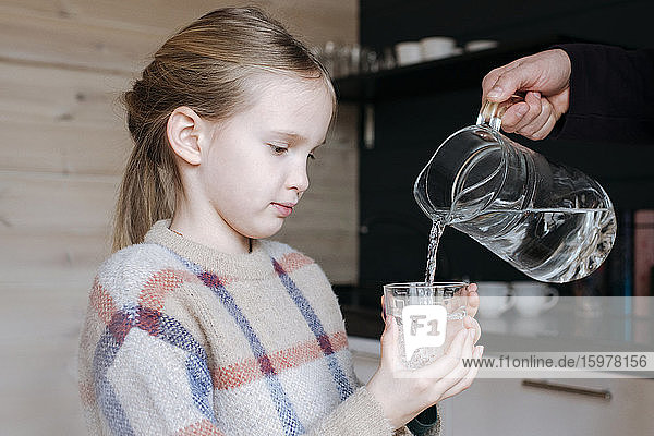 Father pouring water into glass for his daughter in the kitchen