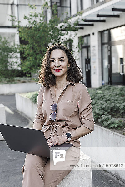 onfident businesswoman using laptop outside office building