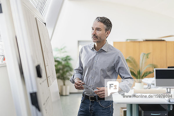 Handsome mature businessman holding eyeglasses while reading strategy on whiteboard at office