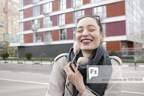 Close-up of smiling woman with white rats on scarf standing against building