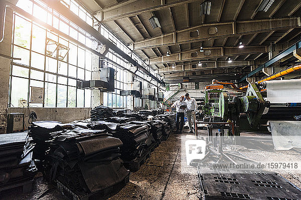 Two businessmen having a meeting in a rubber processing factory