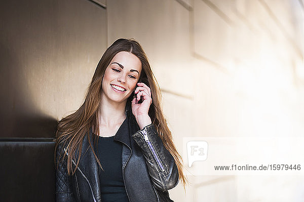 Happy young woman using smart phone by wall in city