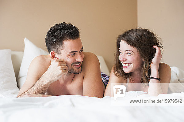 Happy young couple looking at each other while lying in bed at home