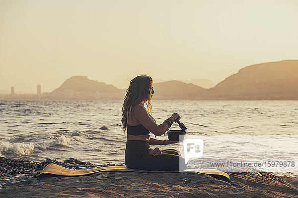 Mature woman meditating with singing bowl practicing yoga at rocky beach in the evening
