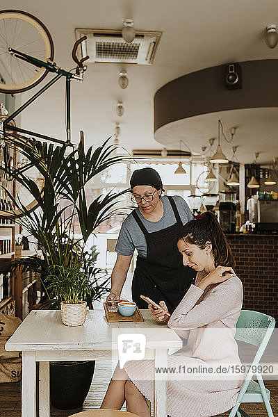 Waitress serving Cappuccino in a coffee shop
