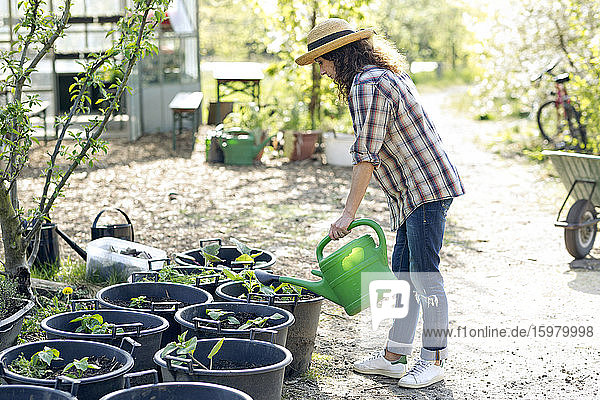 Full length side view of mature woman watering plants while standing at community garden