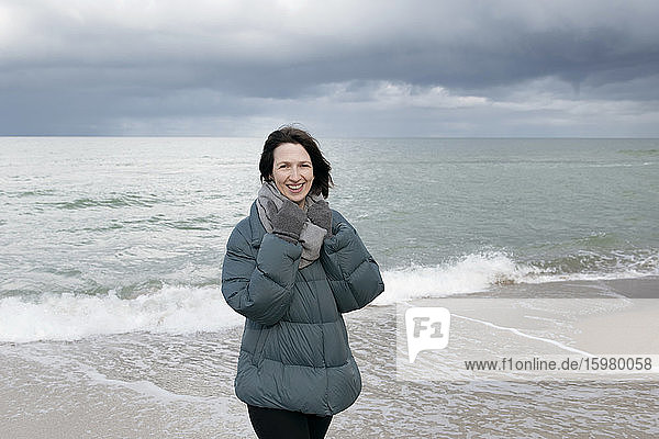 Russia  Kaliningrad Oblast  Zelenogradsk  Portrait of young woman standing on coastal beach and smiling at camera