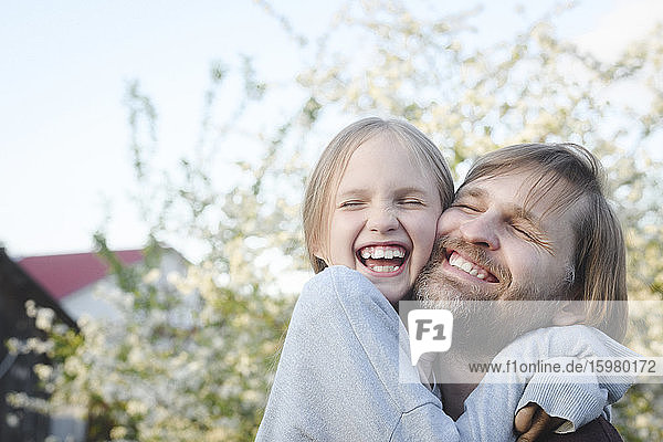 Close-up of cheerful girl embracing father at back yard