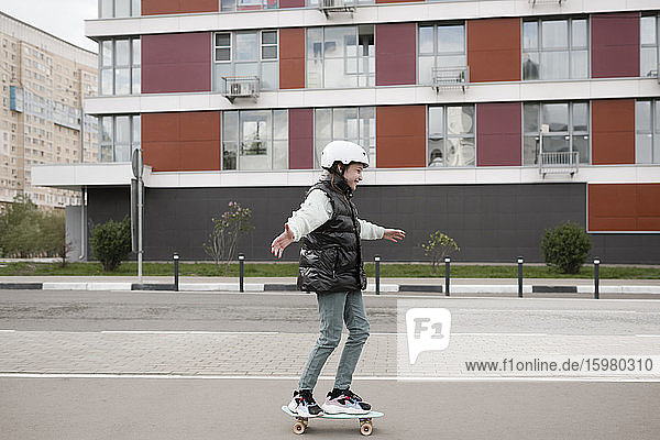 Girl wearing warm clothing skateboarding on road against building