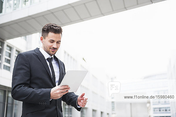 Young businessman using digital tablet outside office building