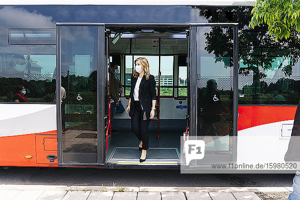Mature businesswoman wearing protective mask getting off public bus  Spain