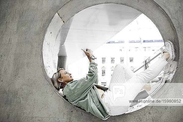 Full length of side view of mature woman using mobile phone while lying on concrete circle in wall