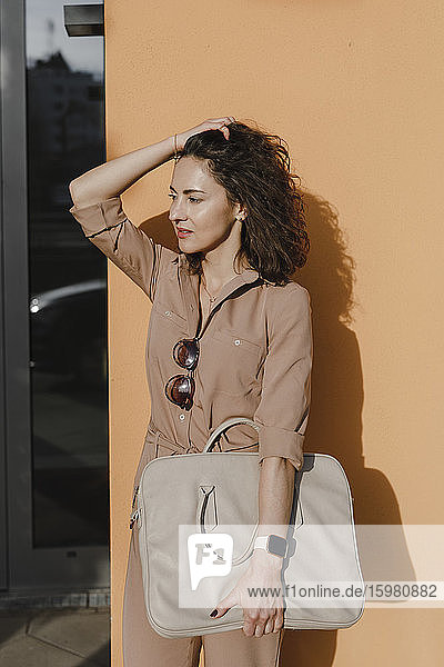Thoughtful businesswoman with hand in hair standing against orange wall