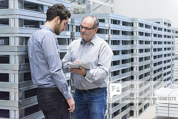 Two businessmen with tablet having a discussion in a factory