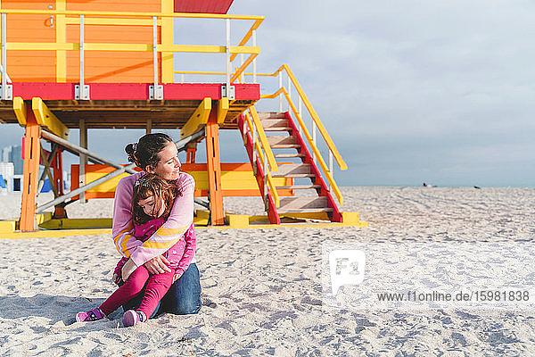 Loving mother embracing daughter at Miami beach  Florida  USA
