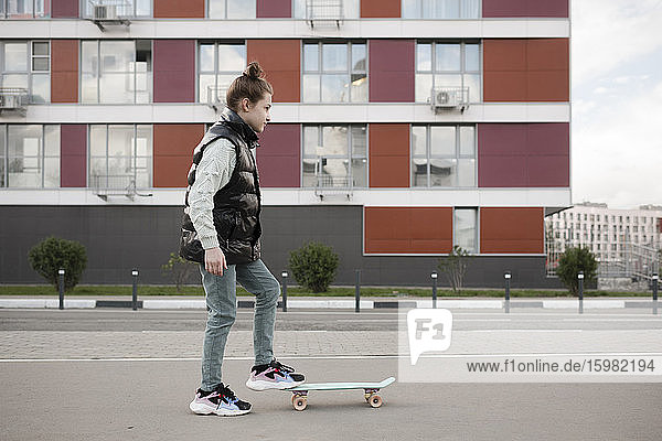 Girl with skateboard standing on road against building in city