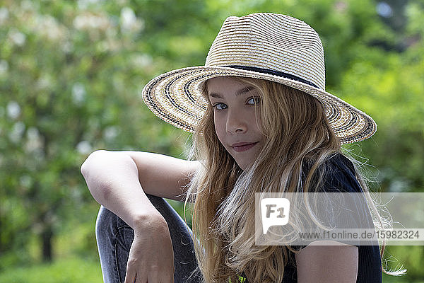 Close-up of girl wearing hat sitting against trees in park