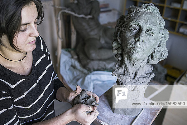 Female student forming clay for bust