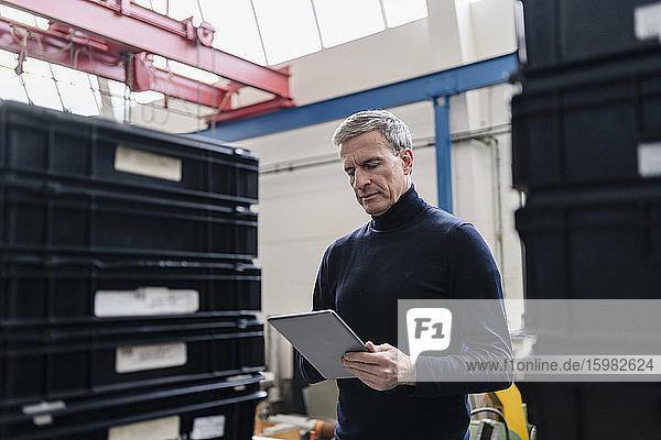 Male supervisor using digital tablet in factory