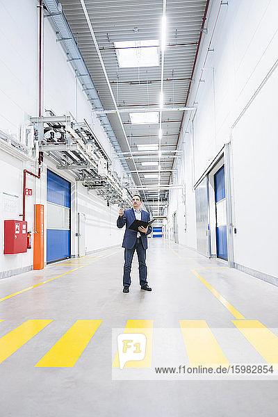Businessman holding folder on factory corridor